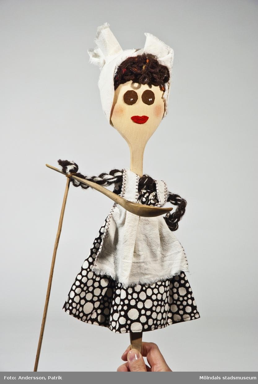 """Docka från """"Sagan om pannkakan"""". Den föreställer modern som lagar till den rullande pannkakan. Kroppen är gjord av en träslev. Dockan har brunt garnhår och en vit huvudduk. Armarna är gjorda av tvinnat brunt och vitt garn. Den högra armen """"håller"""" i en mindre träslev och är dessutom fäst till en träpinne som man kan hålla i för att göra armrörelser. Dockan har också ett vitt förkläde och en brun klänning med vita prickar i olika storlekar.Givaren Blanka Kaplan var förskollärare och använde dockte-ater i sin pedagogik. Hon var ledare för dockteatern """"Tusen-sköna"""" som spelade klassiska sagor i tjeckisk tradition. Blanka Kaplan är född i Tjeckoslovakien och kom till Sverige 1968. De sista åren före sin pension åkte hon runt i olika förskolor med sina föreställningar. (se bilaga i arkiv)."""