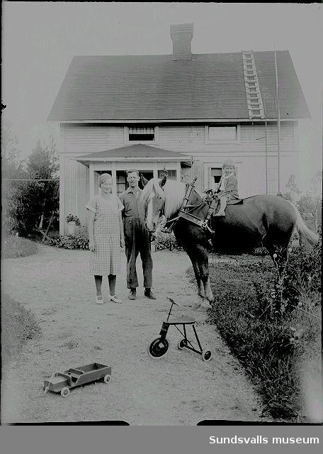 Familj framför bostadshuset, barnet sitter på arbetshästen.