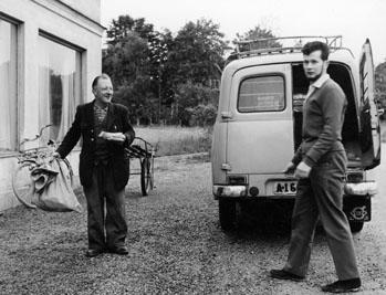Lantbrevbärare Ruben Carlsson har fått en postsäck av transportören postiljon Leif Sverndal från Danderyd.