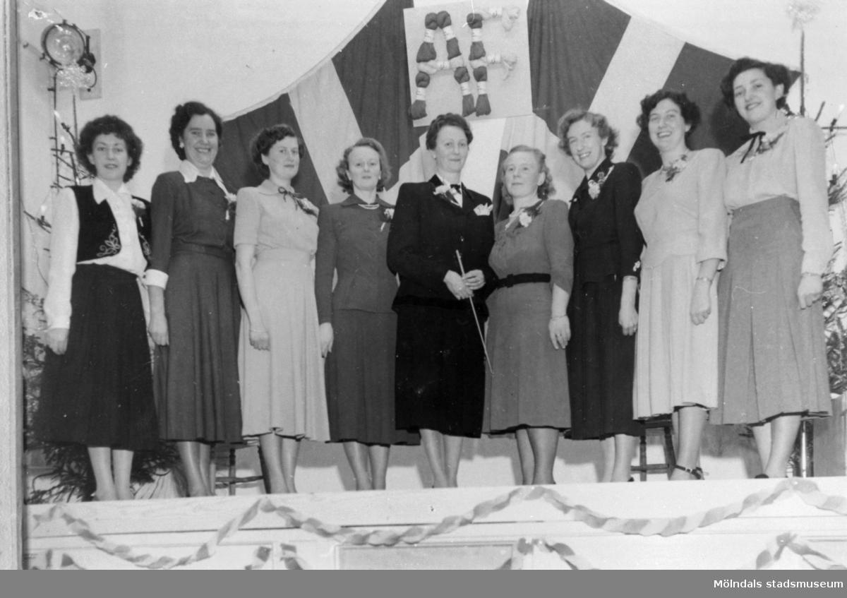 Lindakören med Märit Åshammar. Anderstorps fabriker 1949. I  bakgrunden syns flaggmontage med bokstäverna AF. Dessa är formade av härvlat garn. (Härvel = ett textilredskap som består av en roterbar garnställning av trä, oftast på fot. Känt sedan vikingatid.)