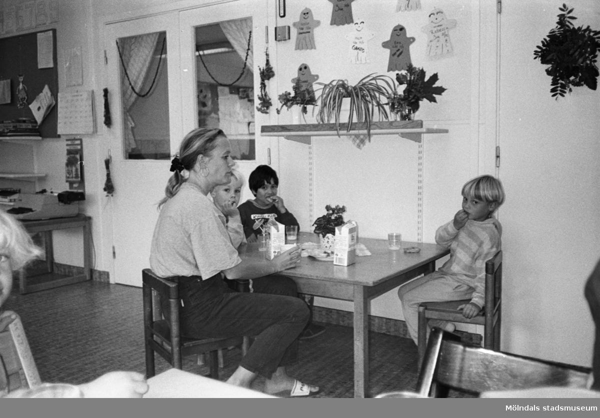 En kvinnlig förskollärare och tre pojkar sitter inomhus vid ett lågt fyrkantigt bord och fikar på Katrinebergs daghem. Ovanför dem på väggen sitter några uppklistrade teckningar samt en uppsatt hylla med växter på. Snett i bakgrunden till vänster syns ett par fönsterdörrar.