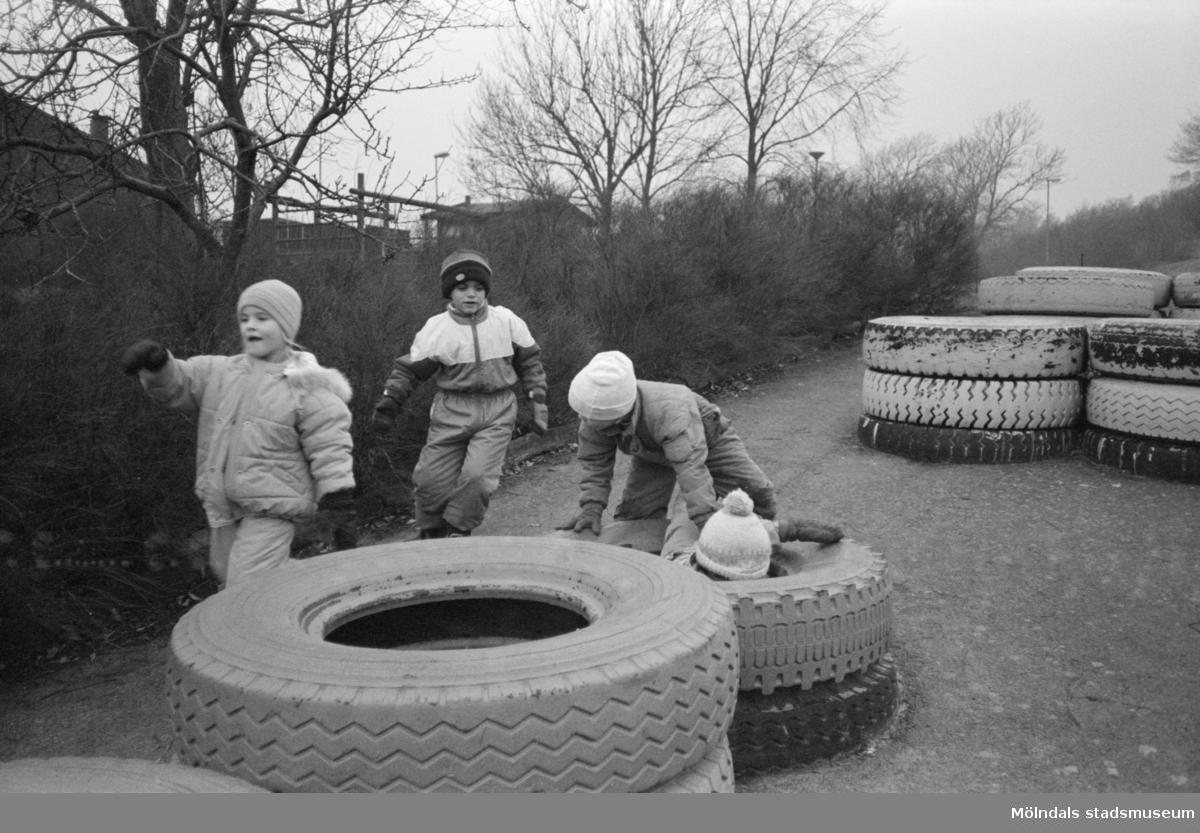 Fyra barn leker utomhus bland stora traktordäck som ligger två och två på varandra vid Katrinebergs daghem. Ett utav barnen sitter på marken, innanför två däck. I bakgrunden finns flera däck som ligger två och två.