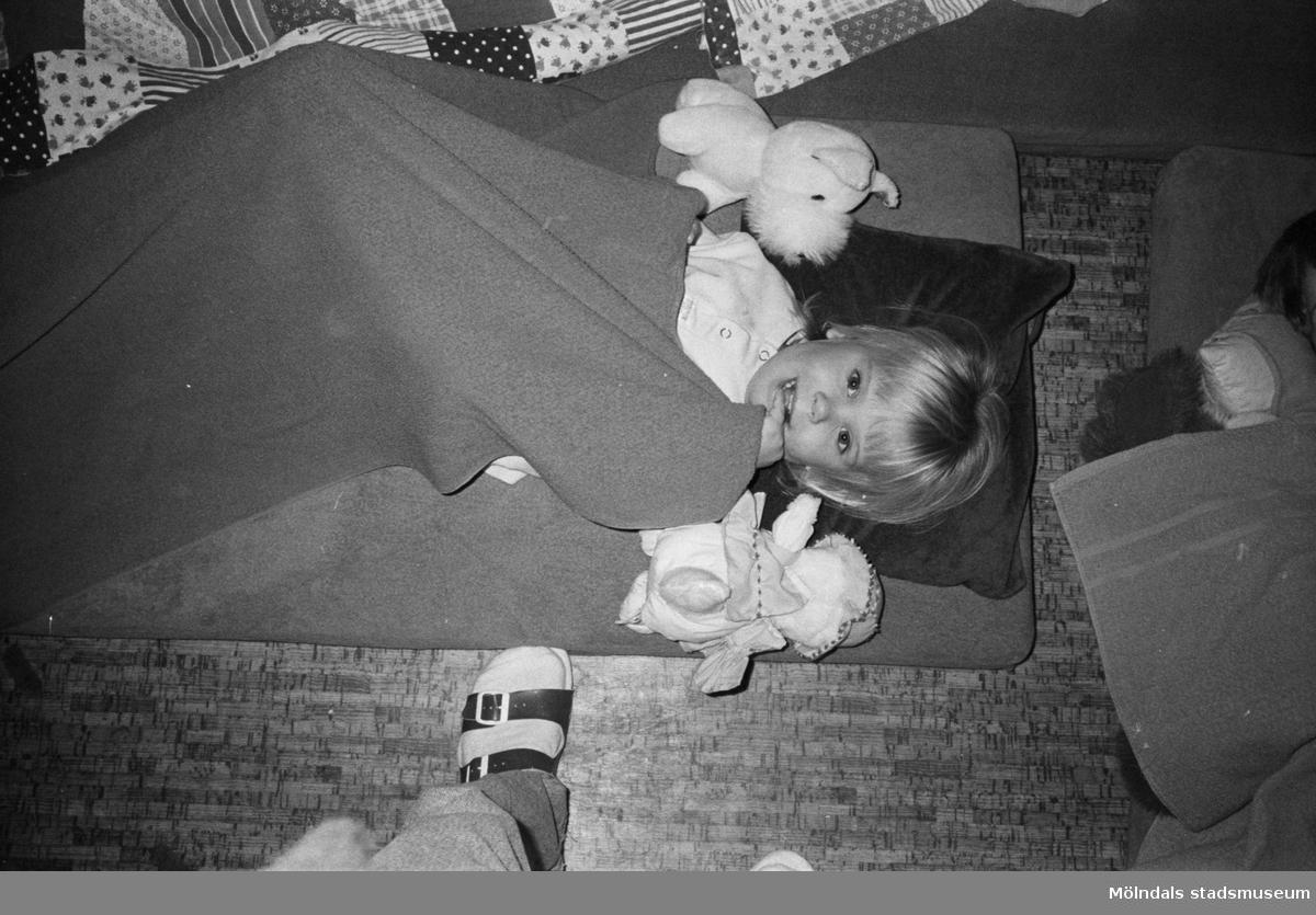 Ett barn ligger på en madrass placerad på golvet. Barnet tittar mot fotografen och har en filt över sig. På varje sida om barnet ligger ett gosedjur. Man skymtar foten och benet av läraren som har tagit bilden. Lille Skutt, Katrinebergs daghem, 1992.