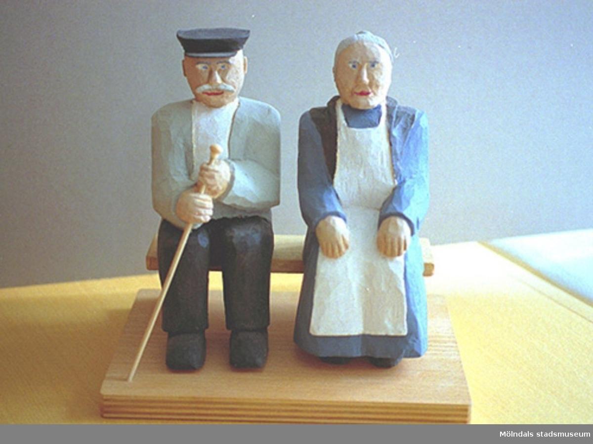 """En äldre gubbe och gumma sitter bredvid varandra. Gubben har hatt och håller en käpp i handen. Gumman är klädd i vitt förkläde och har lagt sina händer i knät. Harry Bergmans """"gubbar"""" (träfigurer)."""