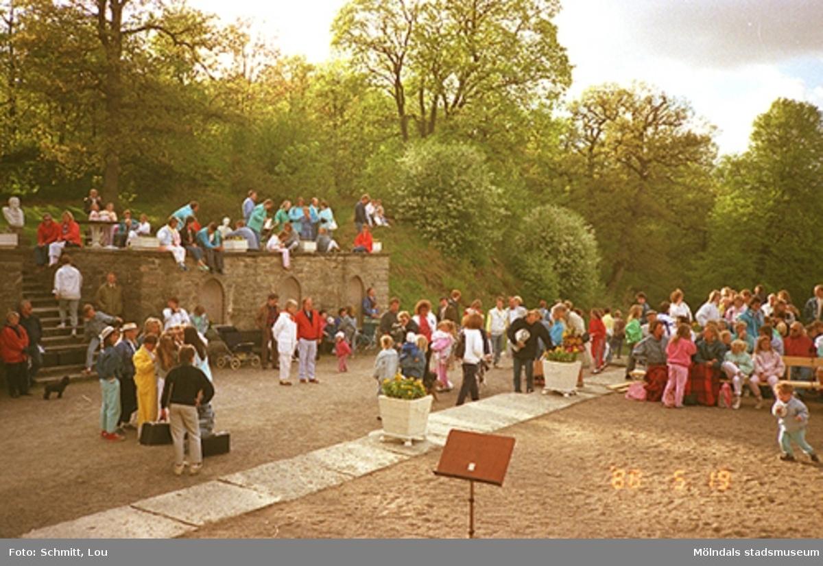 Människor som står eller sitter på Gunnebo slotts framsida. Det ser ut som att de inväntar någon uppträdande eftersom de pratar med varandra och ett barn leker på grusplanen.