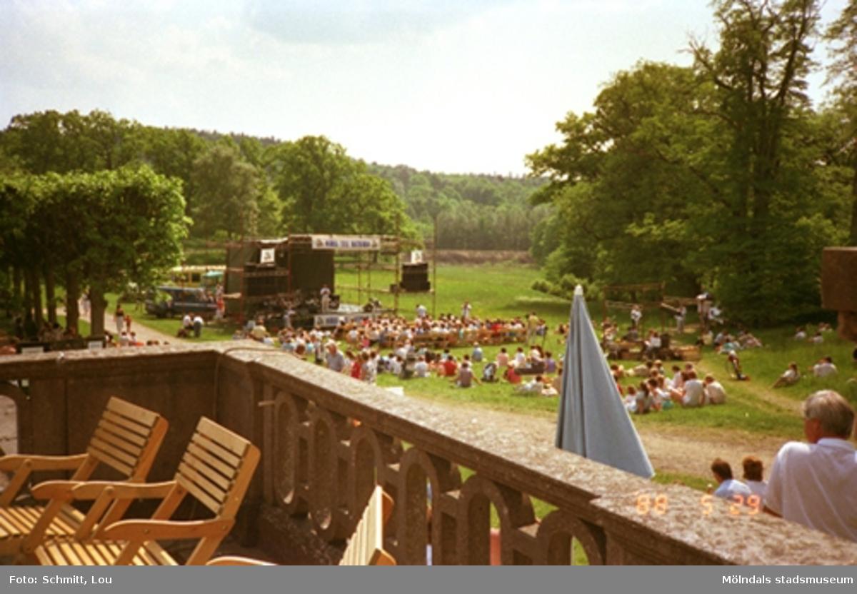 Människor sitter på gräsmattan och lyssnar till Lasse Berghagen. En tillfällig scen är uppbygd för evemenaget. Gunnebo slotts terrass, på baksidan.