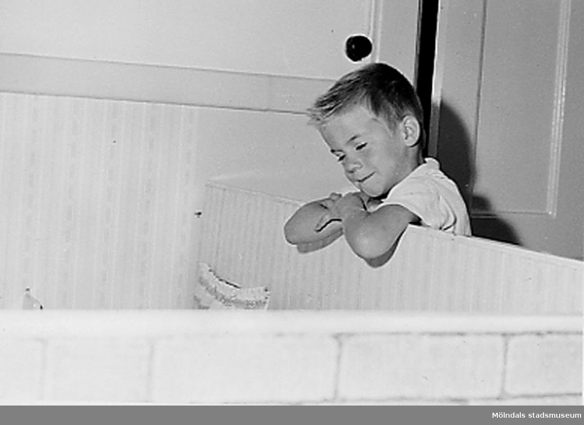 En pojke som lutar sig mot en koja vid Holtermanska daghemmet 1953.