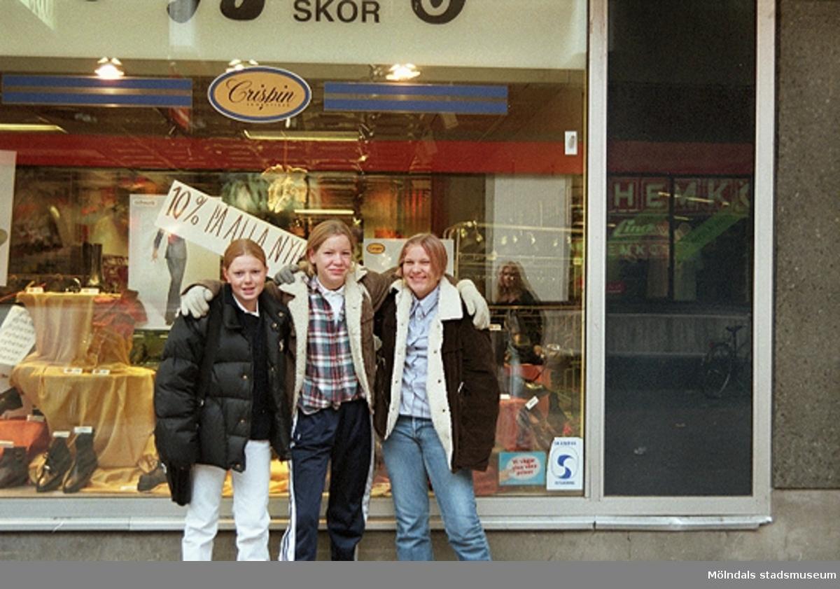 Tre ungdomar poserar framför Nygrens skor på Brogatan. Mölndalsbro i dag - ett skolpedagogiskt dokumentationsprojekt på Mölndals museum under oktober 1996. 1996_1283-1300 är gjorda av högstadieelever från Åbyskolan 8A, grupp 3. Se även 1996_0913-0940, gruppbilder på klasserna 1996_1382-1405 och bilder från den färdiga utställningen 1996_1358-1381.