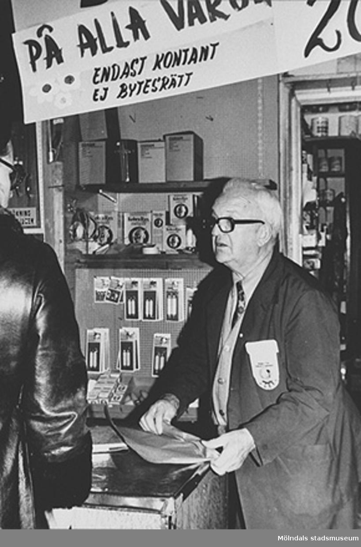 """Bröderna Karlssons Järn-Färghandel är under utförsäljning 1973. """"20% på alla varor. Endast kontant. Ej bytesrätt."""" Expediten är David Heijel."""