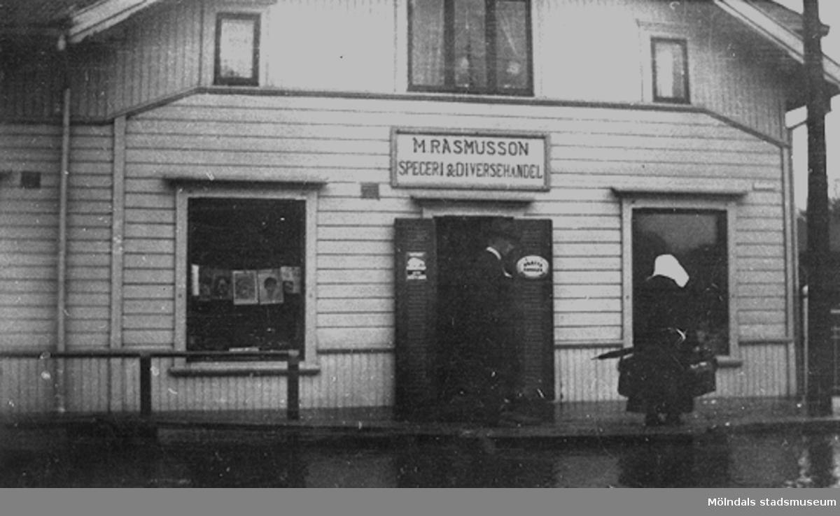 En kvinna är på väg in i speceriaffären. Man ser husets norra gavel (mot bron) på Kungsbackavägen 1.