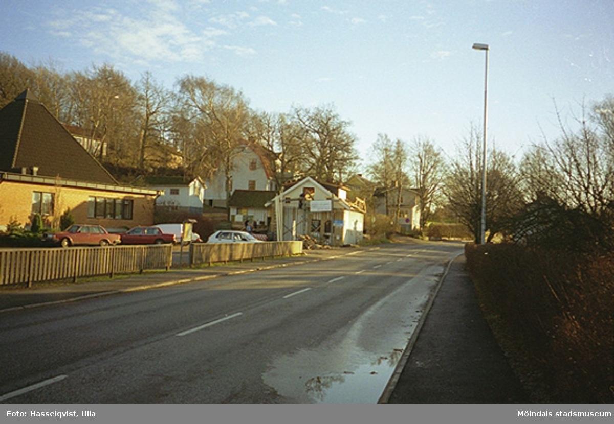 Det vita trähuset utefter vägen ligger på Gamla Riksvägen 81C i Kållered. Längst till vänster ses Centrumkyrkans parkering.