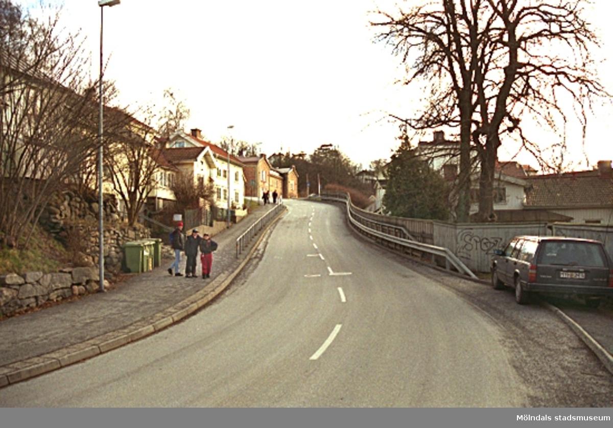 """Längst upp i backen skymtar gamla sjukstugan, f.d polishuset och där Mölndals museum tidigare låg (1986-2002), Norra Forsåkersgatan 19 år 2001. Närmast till vänster ses """"Börje-Magnus"""", ett bostadshus från 1700-talet som byggdes ut på 1930-talet. Huset har fått sitt namn efter Börje Magnus Andersson som arbetade på Korndals fabriker. Nästa byggnad är """"Pannemans"""" som byggdes av en tysk man som drev ett sockerbruk. Efter detta ligger """"Kiste-Pers"""". Här bodde en man som kallades Kiste-Per och som byggde likkistor åt Korndals fabriker. När en arbetare avled fick familjen en kista av fabriken. På höger sida ses Papyrusområdets fastighet."""