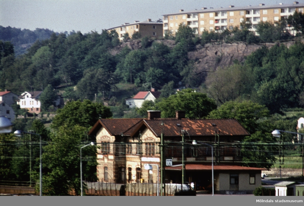 I bildens nederkant järnvägsstationen Mölndals Nedre vid Järnvägsgatan i Mölndal, 1970-tal. I ovankant fastigheter vid Lövgatan och Delbancogatan.