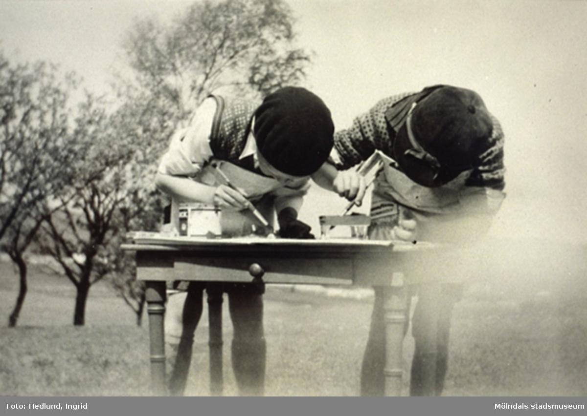 Två barn målar vid ett bord på Bosgårdens barnträdgård, någon gång under åren 1938 - 1945.