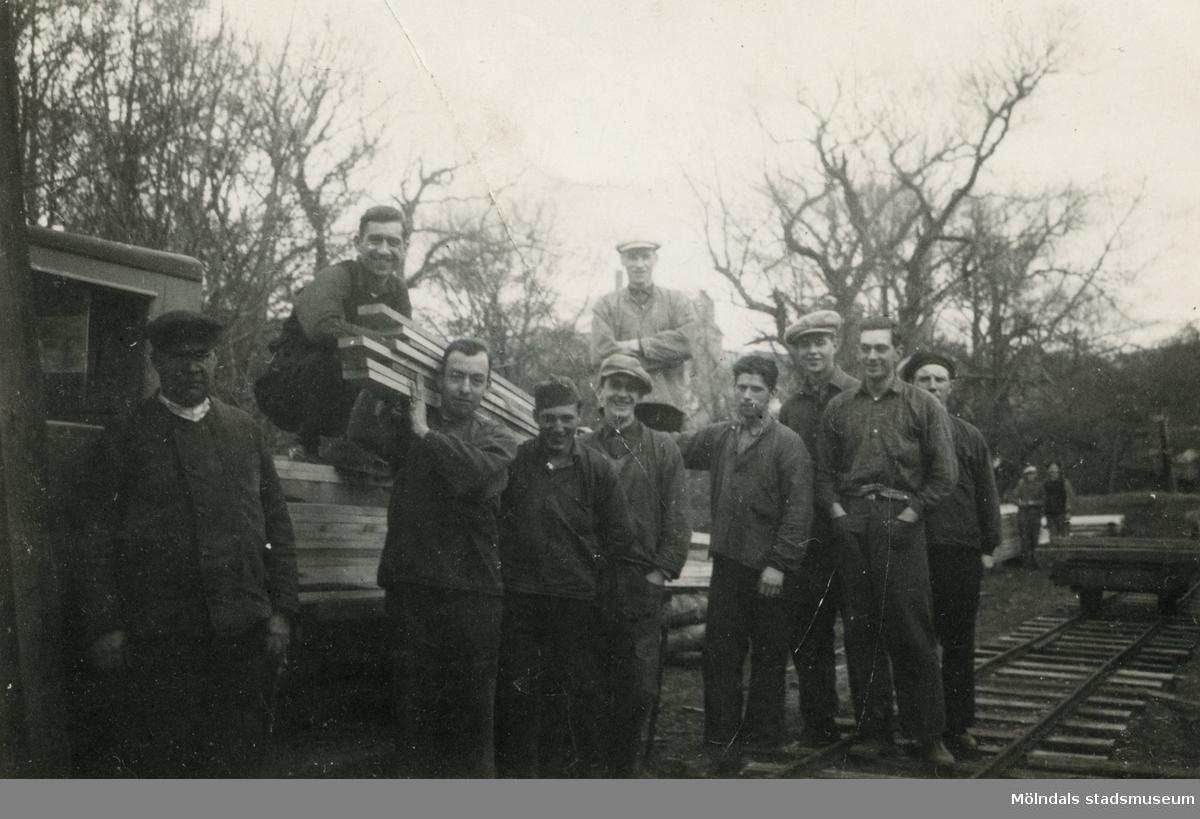 """En samling män uppställda för fotografering utomhus vid ramverkstaden på Papyrus.Birger Andersson (1909-2004), tvåa från höger, arbetade på Papyrus mellan 1924-1976. Hans arbetsplats var ramverkstaden där de spikade lastpallar och """"bottnar"""", som användes för att skydda pappret vid packningen med stålband. Under sina 52 år i ramverksta'n spikades bottnarna för hand i ca 30 år. Resterande tid med hjälp av spikmaskin. Birger Andersson var spikare."""