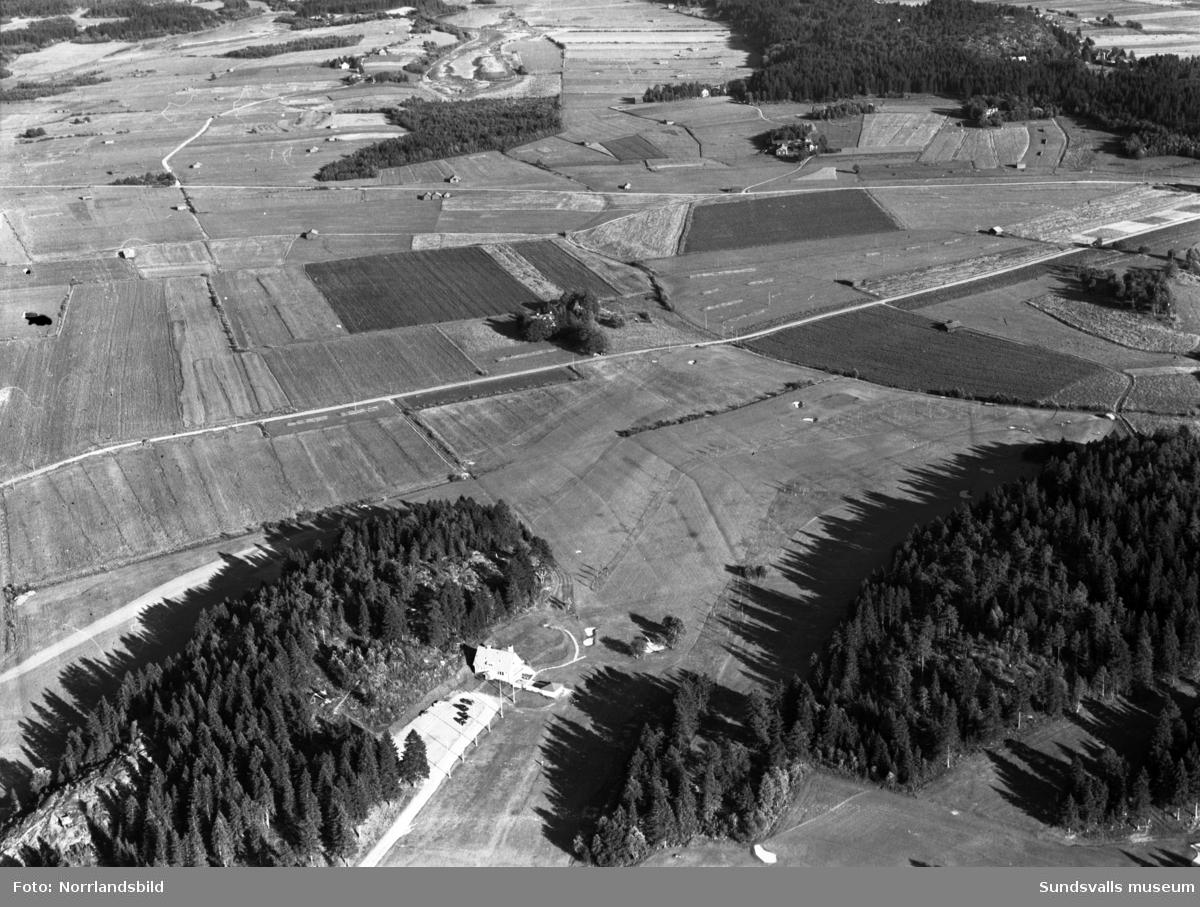 Flygfoton över Skottsunds golfbana med omgivande bebyggelse. På båda bilderna syns golfbanans klubbhus, på bild två före detta Skottsunds barnhem i centrum vid Skottsundsvägen. Längre upp i bild Junivägen och Kråksta tjärn. I övre högra delen av bilden tre gårdar som fortfarande (2016) finns kvar.