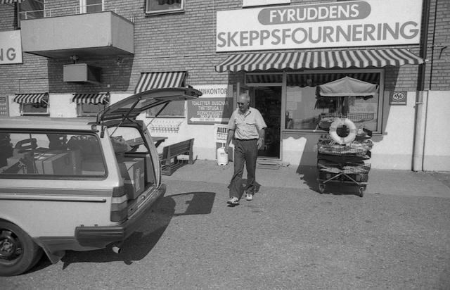 Lantbrevbärare Reinhold Andersson delar ut post till en butik. Tillhör en dokumentation av en lantbrevbärare i trakten av Valdermarsvik av fotograf Ove Kaneberg.