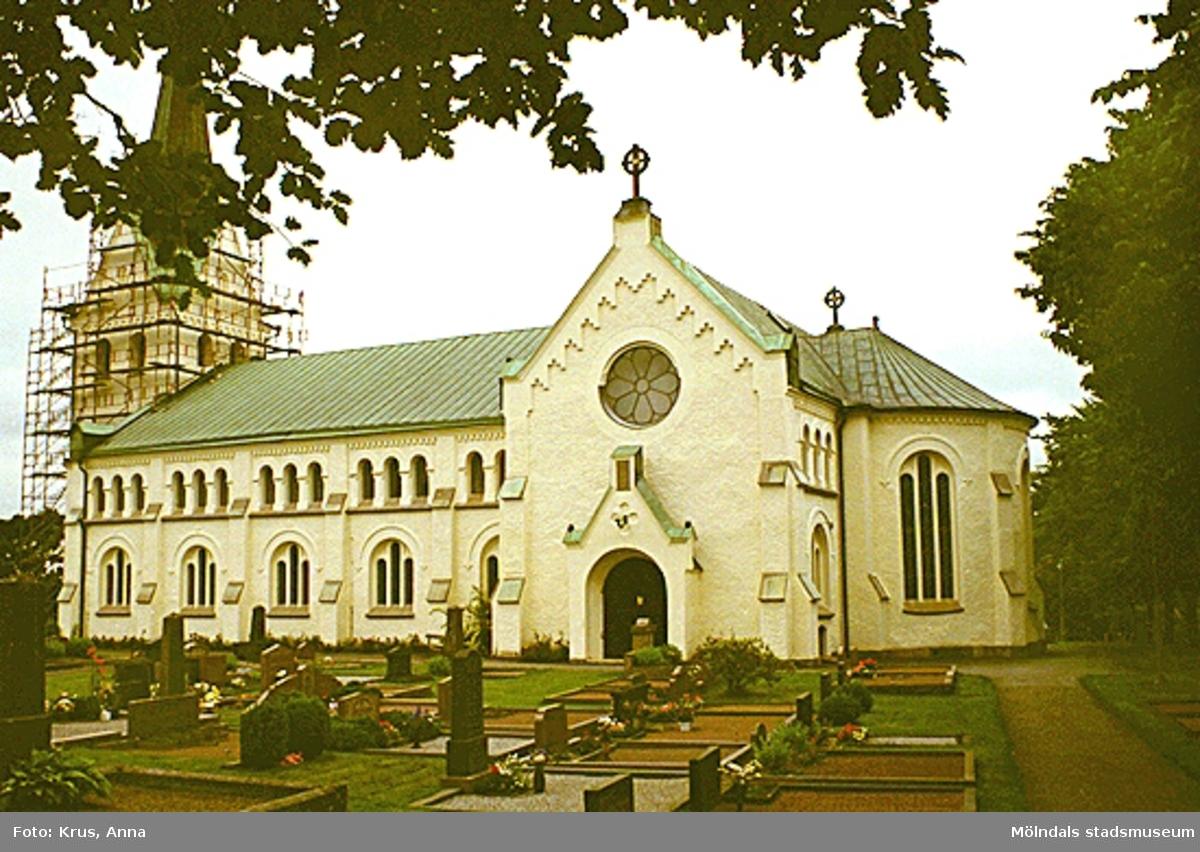 Lindome 11:1. Kyrkan från sydost och gravstenar. Byggnadsställningar runt om tornet som håller på att renoveras.