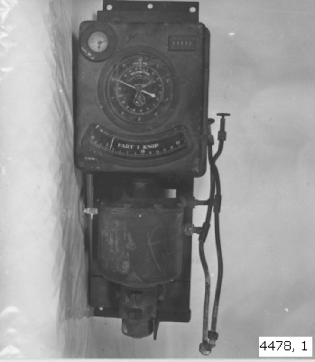 Sallogg huvudinstrument. Till sallogg med tryckhammare av mässing, mörkt gråmålade. Huvudinstrumentet anger å skilda tavlor: Naut. mil 1 -10, klinometer 1 - 18, fart i knop 0 - 16. summa naut. mil samt tiden 1 - 12. Urverket är av mässing och urtaget ur apparaten. Huvudinstrumentet med tryckkammare fastsatt på ställning av plattjärn. Märkning: Svenska Aktiebolaget Logg Stockholm Patent.