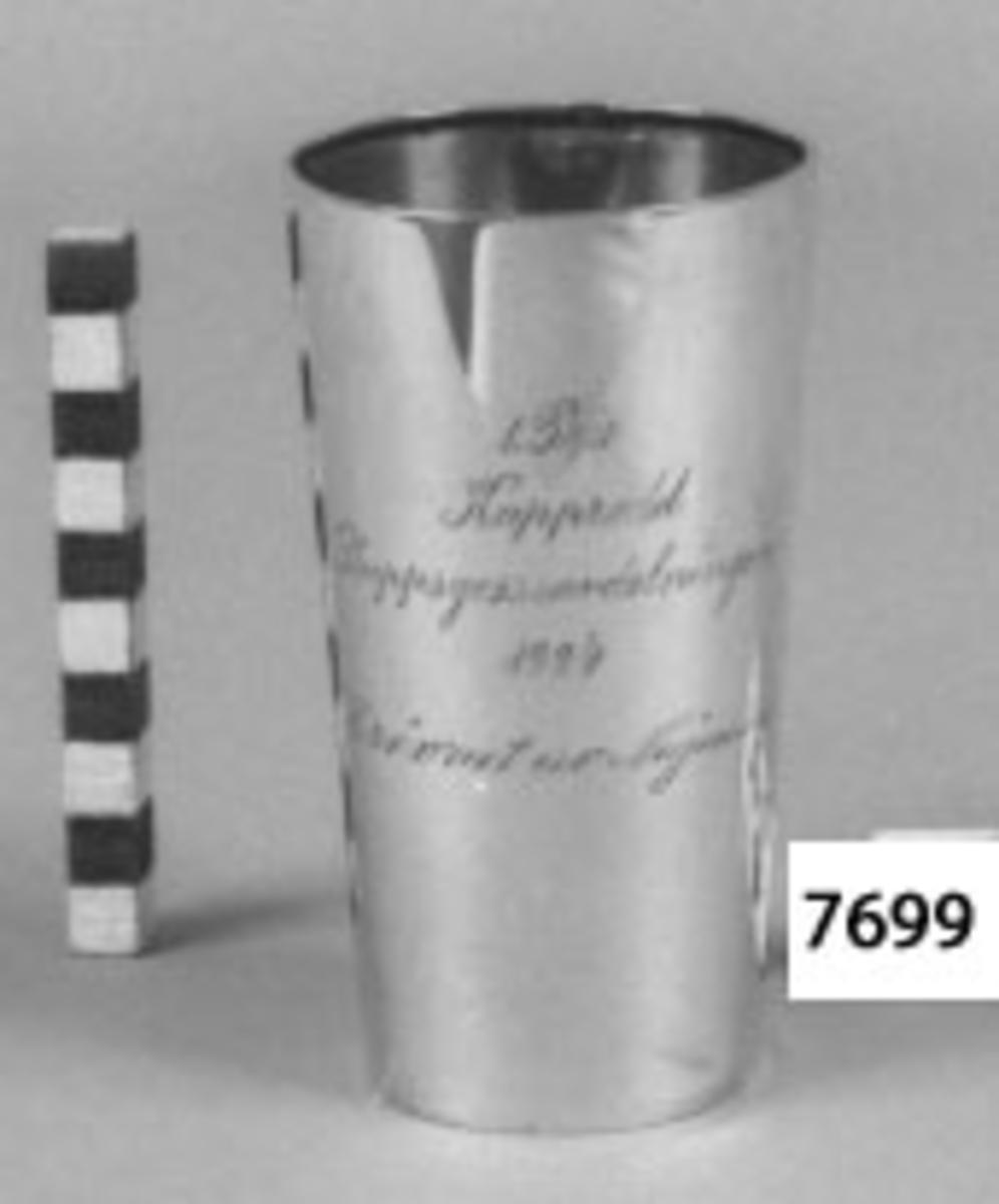 Bägare av silver. Utgör 1:a pris i kapprodd, erövrat av skeppsgossebriggen Najaden 1924. Inskription: 1 Pris Kapprodd Skeppsgosseavdelningen 1924 erövrat av Najaden.