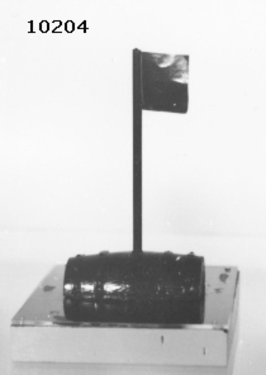 """Modell av """"Vrakboj"""". Tunnan är försedd med fyra stycken band samt en stång med en flagga av plast. Grönmålad. Bojen är monterad på en träplatta, botten och sidorna är ljusgrå, översidan blå, täckt av ett plexiglas."""