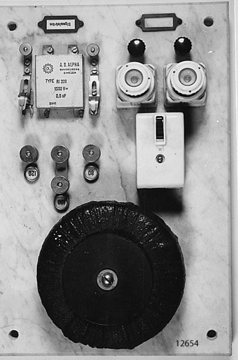 På platta (plint) av marmor, finnes bl. a. motstånd, säkringar, inkopplingsskruvar, strömbrytare och kondensator. Apparaten omkopplingsbar för 80, 100 och 120 volt. Märkning: A. B. ALPHA SUNDBYBERG SEWDEN TYPE RI 206 1500 V = 0.5 uF 3941 Signalström. På baksidan etikett med texten: Signalapparat EH 1570/220  220 volt 25-50 Justerad 1941-11-17 av GHg Kungl Telegrafverkets verkstad Nynäshamn.