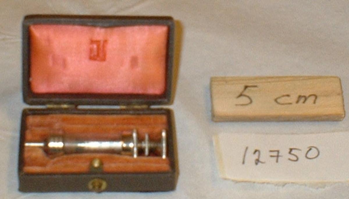 Injektionsspruta 1 ml, av glas och metall, med en nål. Förvaras i svart etui, invändigt klätt med rött sammet.