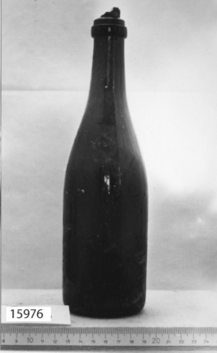 Handblåst flaska i grönt glas. Botten inblåst i flaskan. Flaskhalsen avsmalnad och avslutas med en profilerad kant. I flaskan sitter en bit kork. Utan innehåll.
