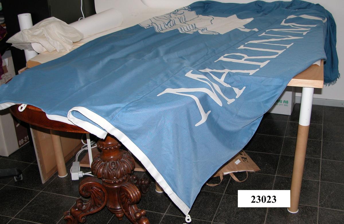 """Flaggans bakgrundsfärg är blå. På flaggans underkant finns texten: """"Marinmuseum"""". Ovanför, strax till vänster, finns den dåvarande logotypen, en gallionsfigur. Text och gallionsfigur är tryckta i vitt. Flaggans yttre ände är något fransad"""