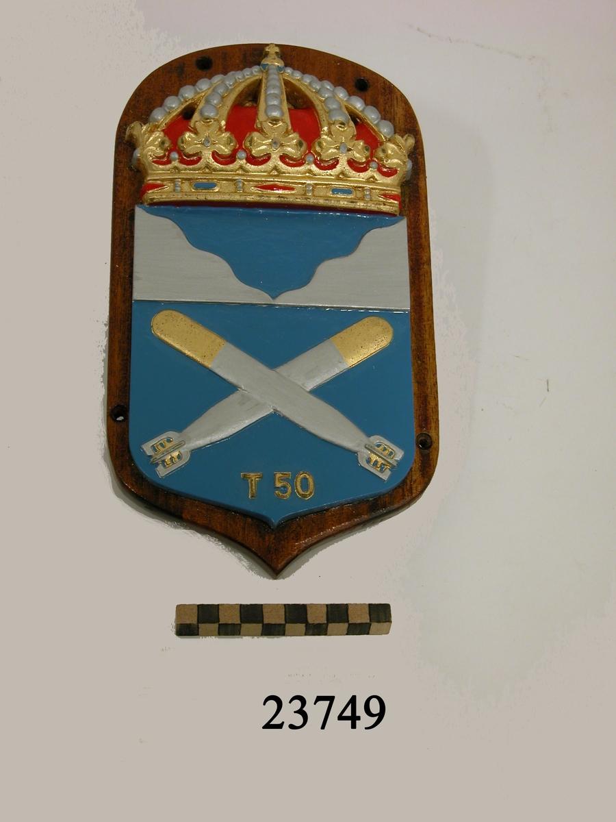 Krönt vapensköld av gjuten mässing monterad på fernissad platta av trä. Emblemet består av blåfärgad sköld som är delad i två fält. I det övre fältet, silverfärgad kustkontur. I det nedre två korslagda torpeder, silverfärgade, spetsarna i guld. Längst ner T50 i relief, guldfärgad. På baksidan skrivet med röd tusch T50.