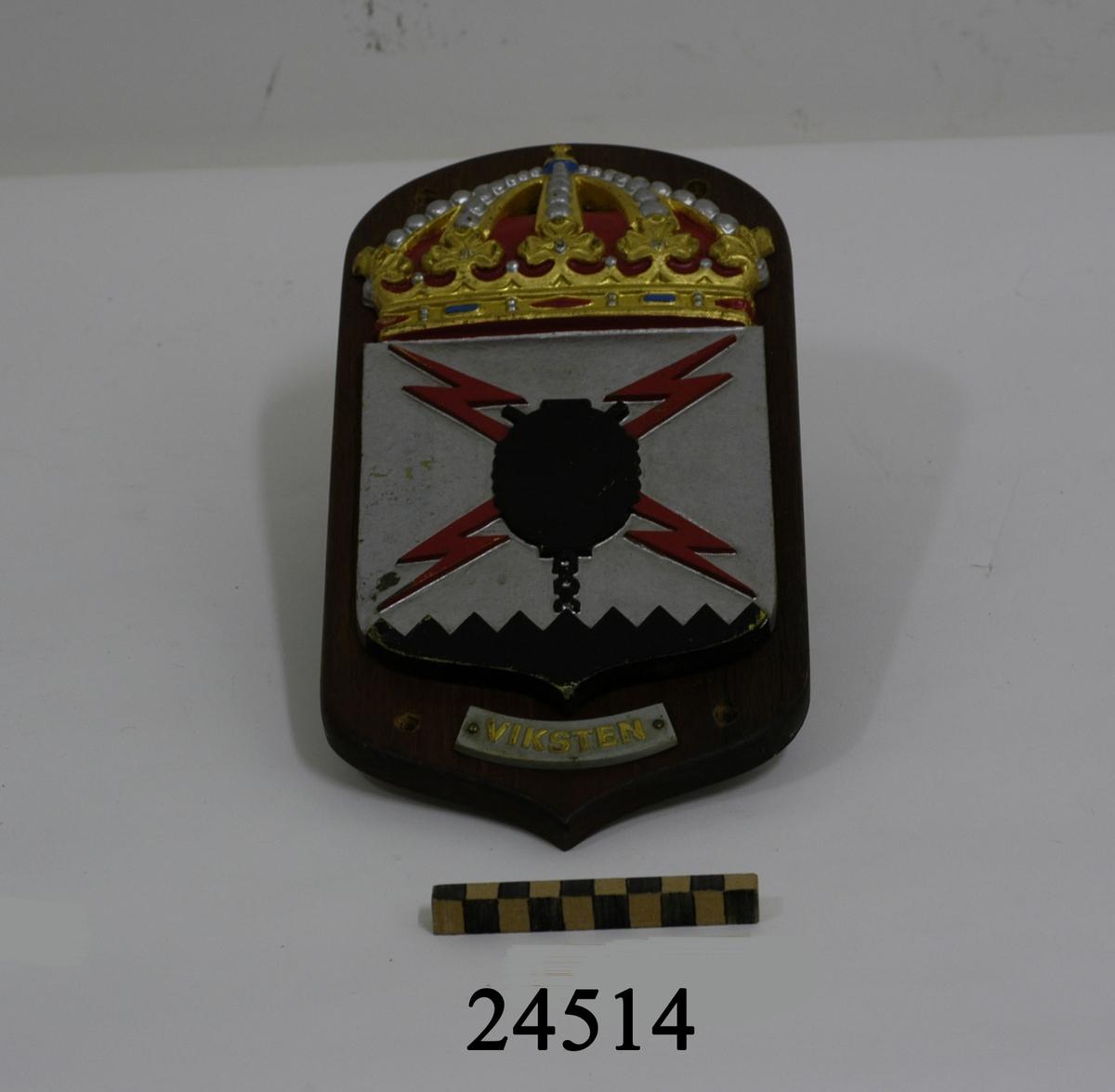 """Vapensköld gjuten av mässing, krönt med kunglig krona, målad i heraldiska färger. Emblemet består av silverfärgad sköld med svart förankrad hornmina. På vardera sida om minan två röda blixtar. Nederst på skölden ett svart fält med taggad överkant. Under skölden en svagt böjd ljusgrå metallbricka med texten """" VIKSTEN """" i guld. I mahognyplattan fyra hål för uppmontering. På baksidan liten ögla för upphängning samt tejpbit med röd text """" Officers Mäss """""""