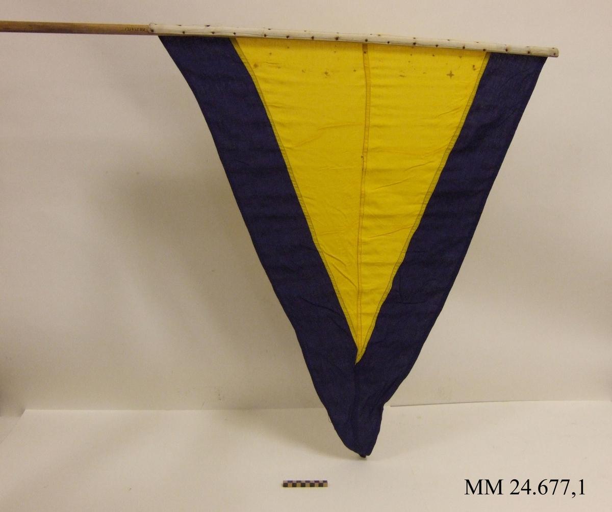 Fartstandert av bomull. Storlek 3. Även standerten Alfa. Trekantig form, gul med mörkblå kant ca 140mm. Vitt lik spikad i rundstav av obehandlat trä. Flaggan ligger i påse tillsammans med tre andra flaggor, sk. fartflaggställ.