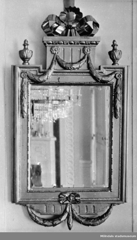 Vägghängd, avlång träspegel med dekor. I spegelglaset ses delar av ett rum samt med kristallkrona. Gunnebo slott 1930-tal.