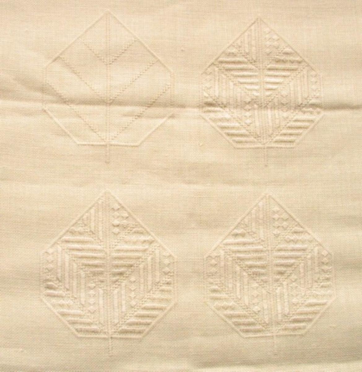 Broderad rektangulär duk. Sydd på Skollinne II med Knox Linens Lace nr 40 till sticksömmen och Knox Linen Floss nr 25 till plattsömmen. Mönstret: Två rader blad som mittbård.