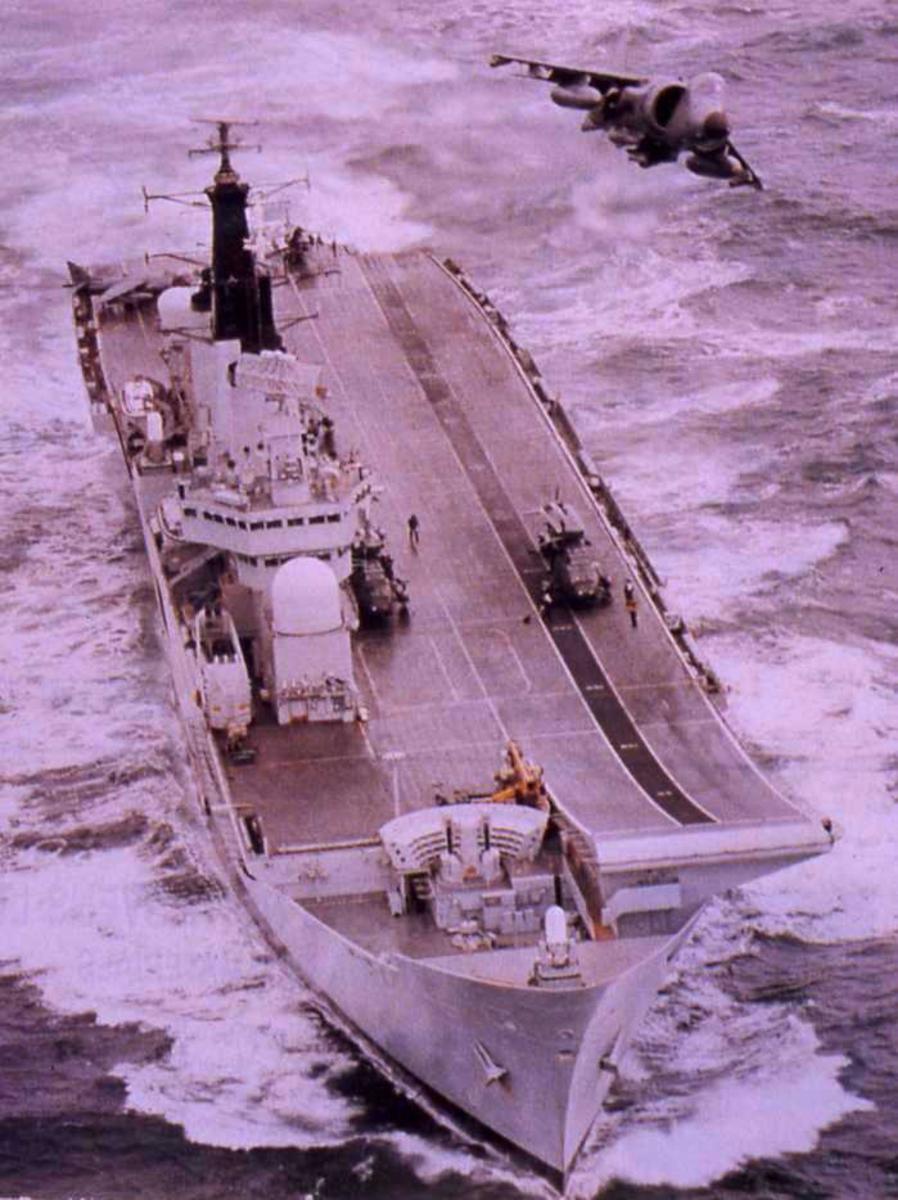 Engelsk hangarskip av Invincible - klassen som heter Invincible med nr. R 05. Ombord sees fly og kjøretøymateriell. I luften over skipet sees et jagerfly.