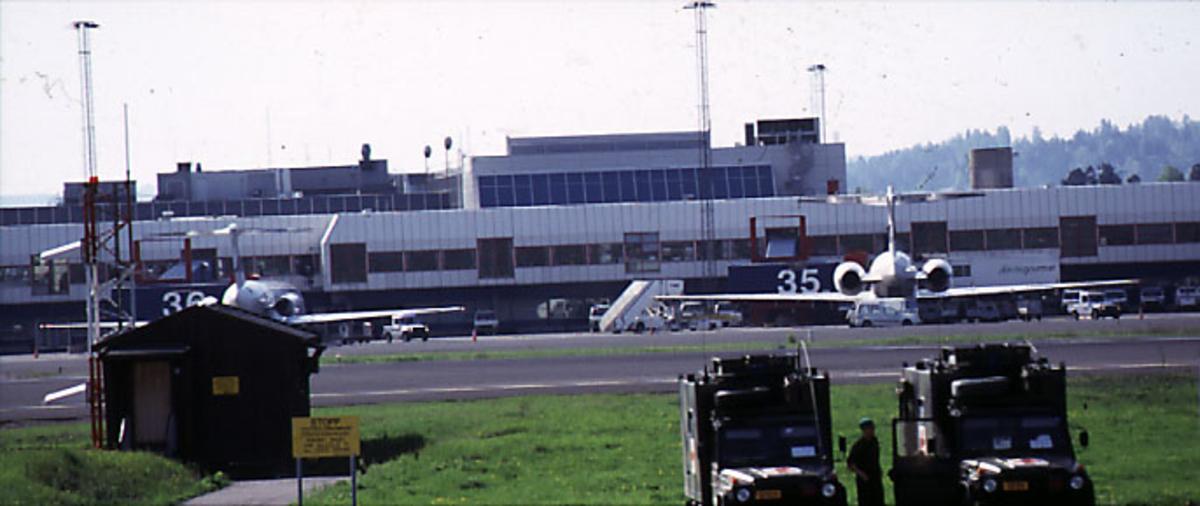 Lufthavn, i forgrunnen 2 kjøretøy fra Røde kors og 1 person i uniform. I bakgrunnen, 2 fly, flere kjøretøyer og terminalbygningen.