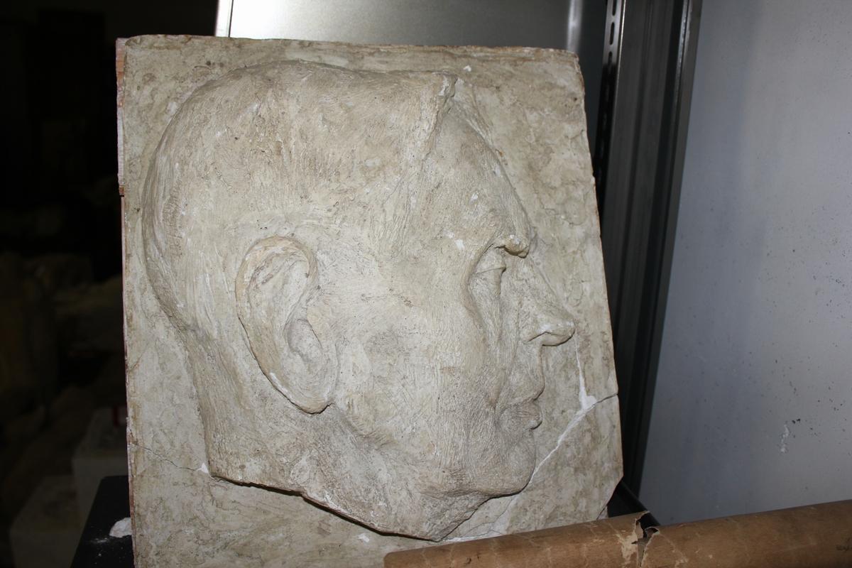 Relieff plate i gips på tre av ett mannsansikt.