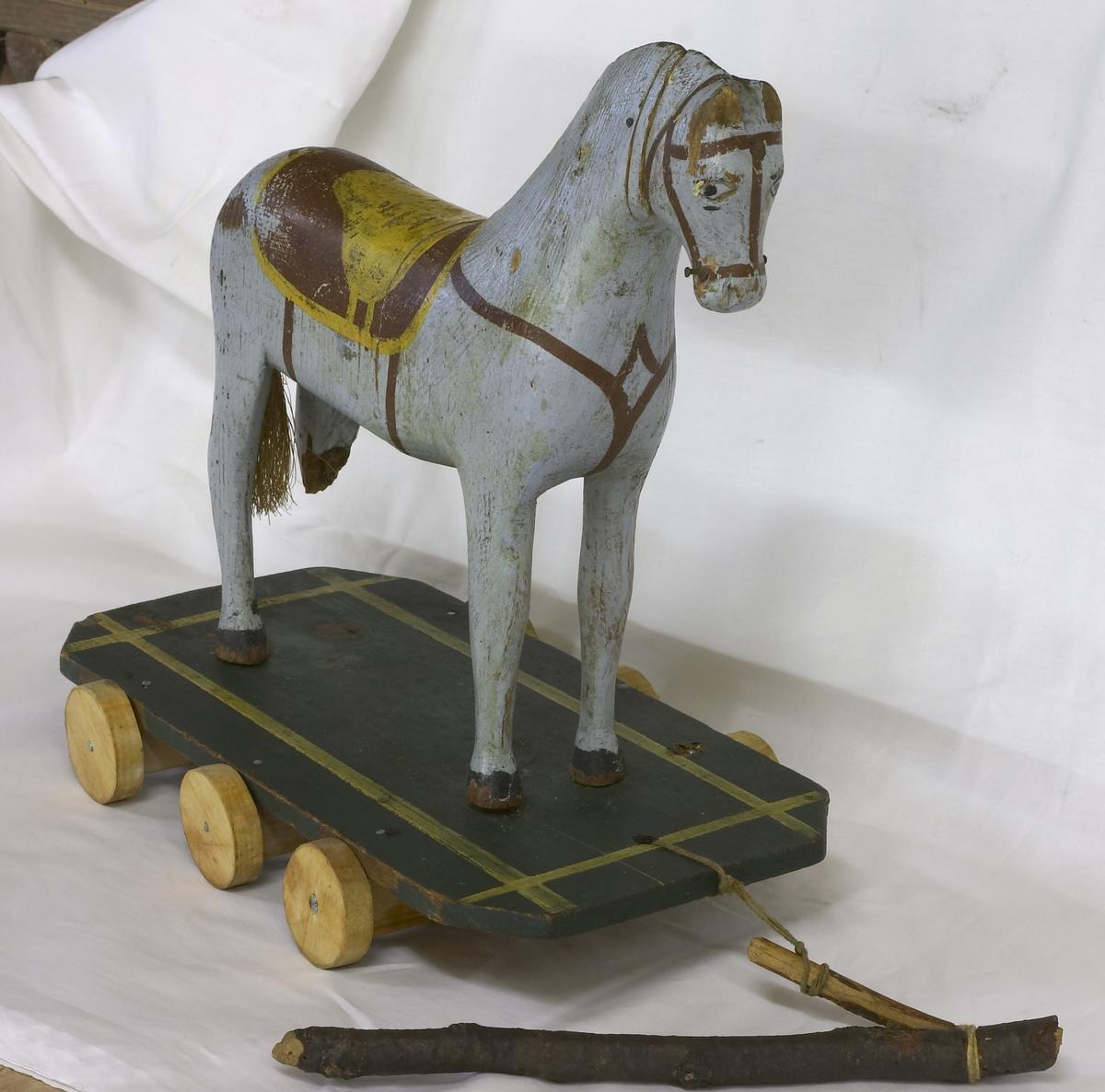"""En lekehest i tre. Mangler ett bein. Står på en platting med hjul. Hesten er malt lyseblå og har påmalt sadel, hodelag og brystreim. Har med en liten""""tømmerstokk"""" til å trekke den med."""
