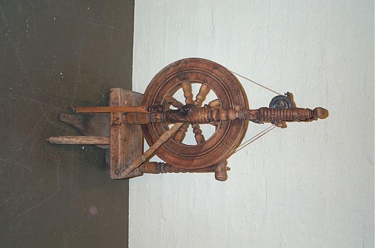 """Form: Eldste type med lite hjul og snella (23) 15: står utover hjula.  Bak snella sto det såkalla rokklag, der ulla vart bunden.  Når ein spann, nappa ein ull av """"røinet"""" på rokklaget, ein karda ikkje rullar."""