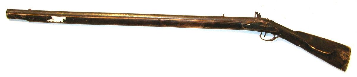 1 flintelaasgevær.  Helskjæftet haglgevær med flintelaas. Ladestok mangler. Jernbøile under avtrekker. Gevær og skæft neppe fabrikarbeide. Løpets længde 92 cm. og indre diameter 1,4 cm  Kjøpt av husmand Ole M. Pladsen, Amble.