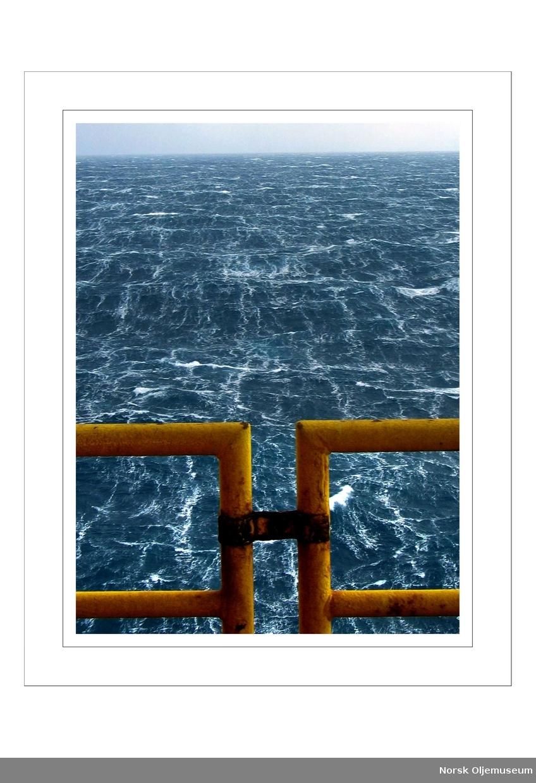 70 knop fra nord.  Bilde tatt av bølger med rekkverk i forgrunn.