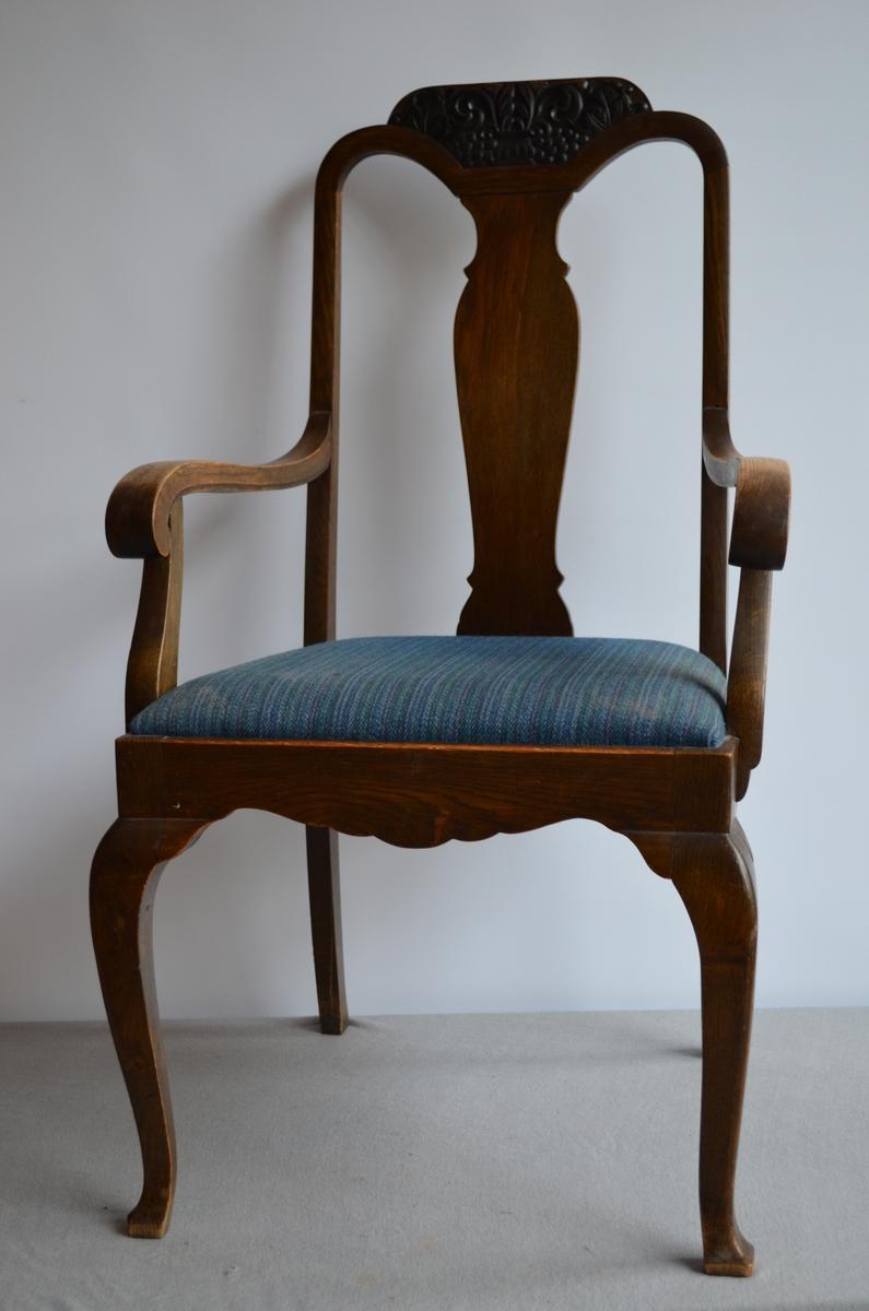 2 identiske stolar med armlener. Setetrekket er truleg trekt om i ettertid. Blåstripete stoff. På topp av stolryggen har treskjæringar (lønneblader og drueklaser).