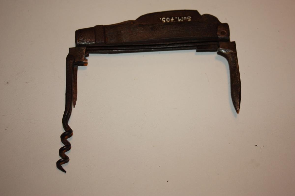 Fallekniv med tre knivar, korketrekkar og eldstål. Skjefteplater av tre. Breidast på midten