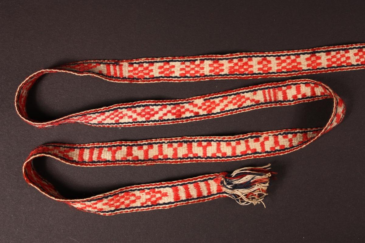 Grindvove lindeband i raud ull og kvit lin. Duskar i endane. Variert mønster.