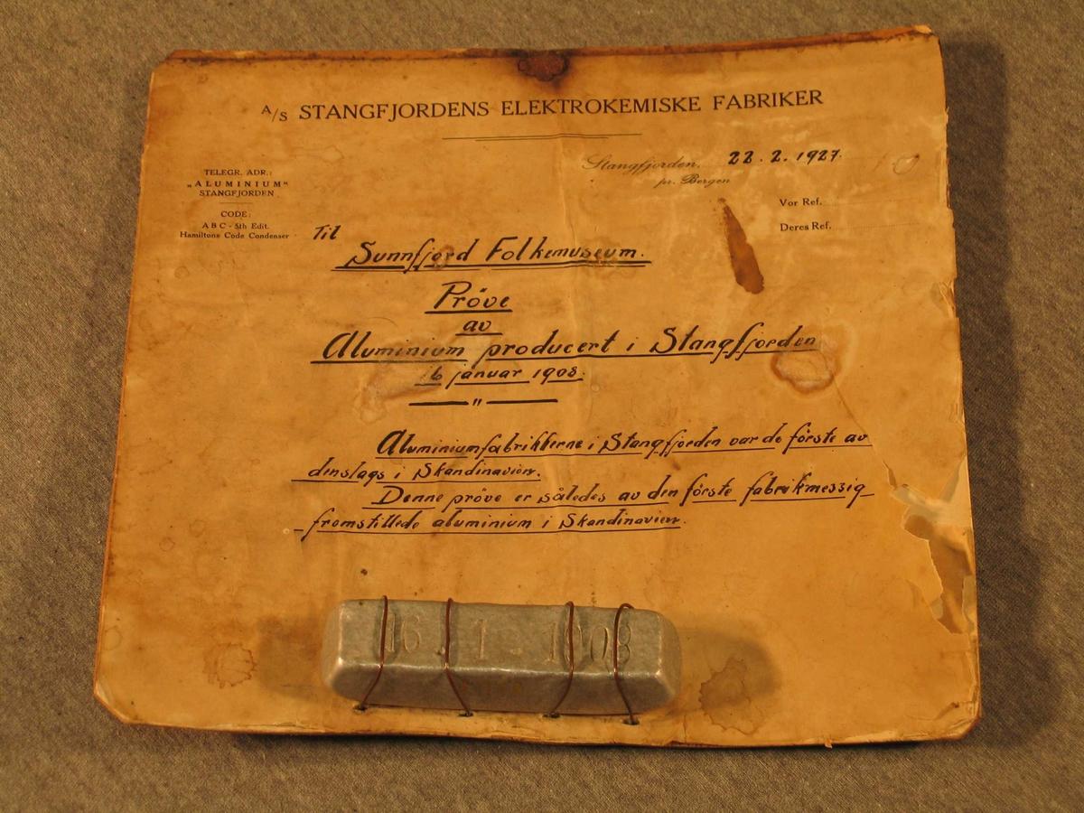 Rektangulær aluminiumsbarre frå første produksjonen i Stongfjorden 1908. På barren er trykt 16.01.1908. Barren er festa med streng til eit gåvebrev som er festa på papp. Det ser ut til å ha vore ei metallhempe på pappen slik at brevet kunne henge på veggen.
