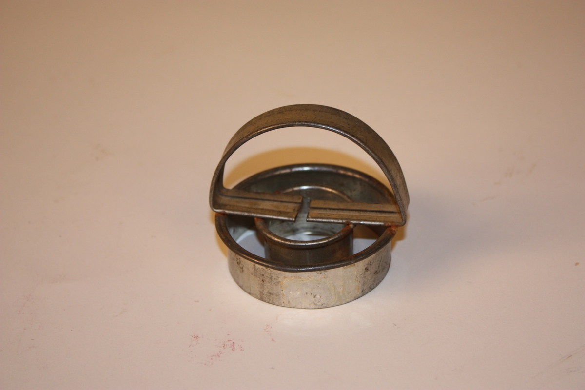 To skarpe stålringar som er lodda saman med eit halvsirkelforma handtak