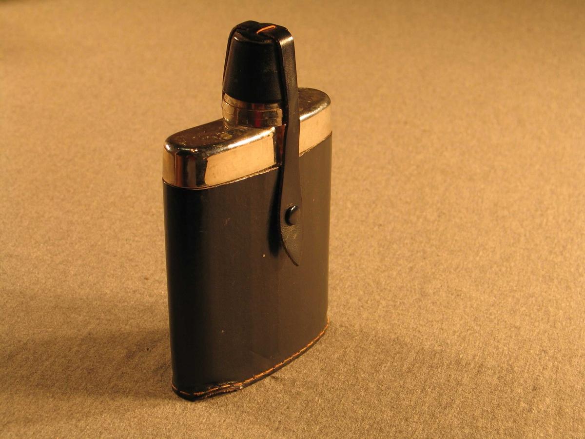 Brennevinslrke med skinnetui og skinnhette over korken. To drammeglas i korken. Blekkomslag på flaska for å illudere metallflaske.