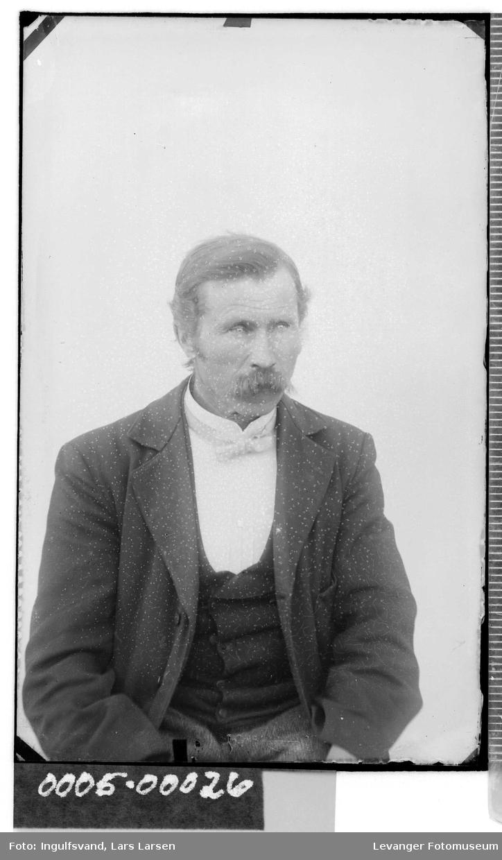 Portrett av mann  med bart og sløyfe.