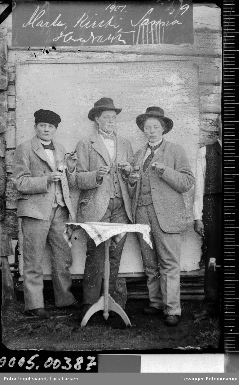 Gruppebilde av tre kvinner utkledd som menn,med drammeglass, foran et bord.
