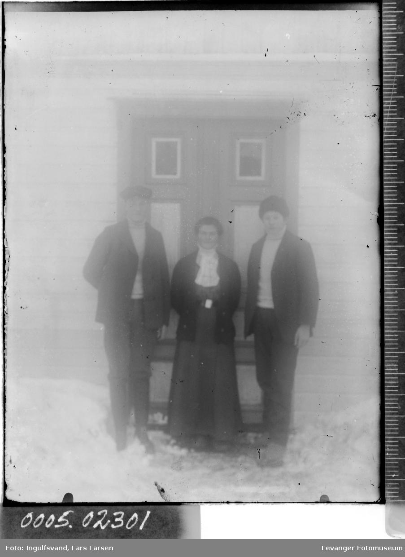 Gruppebilde av tre ungdommer foran et inngangsparti.